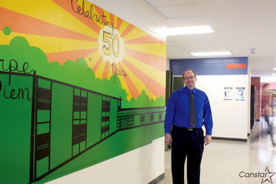 Murdoch MacKay Collegiate principal Darwin MacFarlane is shown by the new mural marking the school's 50th anniversary.