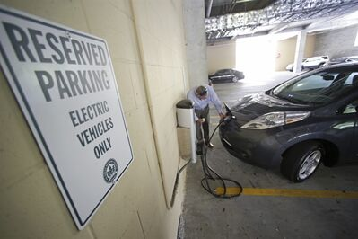 This Sept. 4, 2013 photo shows Orlando Mayor Buddy Dyer connecting a charging cable to a new electric rental car in Orlando, Fla. On Thursday, Sept. 5, Orlando will be home to a first-of-its-kind electric rental car initiative where hotel partners will valet park the electric rental for free and charge it for you. (AP Photo/John Raoux)