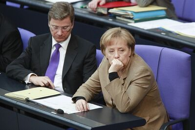 FILE - In this Feb. 26, 2010 file picture German Chanceller Angela Merkel, right, and Vice Chancellor and Foreign Minister Guido Westerwelle listen to a debate about the German Afghanistan mission at the Parliament Bundestag in Berlin, Germany. Germany boasts the world's most powerful woman, Europe's most powerful economy and an industrial machine that's the envy of the world but ahead of Sunday, Sept. 22, election neither incumbent Angela Merkel's conservative forces, nor her center-left rivals _ nor indeed the German people at large _ have any appetite to take center-stage as a European or global leader. (AP Photo/Markus Schreiber,File)