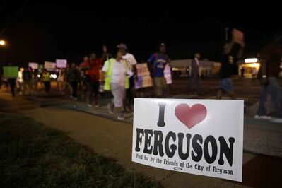 Protesters march Thursday night in Ferguson, Mo. Protesters again gathered Thursday evening, walking in laps near the spot where Michael Brown was shot. Some were in organized groups, such as clergy members. More signs reflected calls by protesters to remove the white prosecutor from the case.