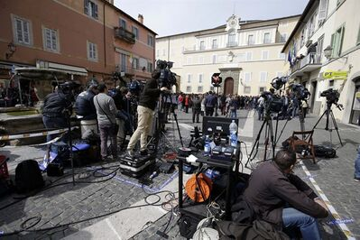 "Journalists and TV crews stand in front of the papal residence in Castelgandolfo, in the outskirts of Rome, Saturday, March 23, 2013. Pope Francis traveled Saturday to this hilltown south of Rome to have lunch with his ""brother"" and predecessor Benedict XVI, an historic and potentially problematic melding of the papacies that has never before confronted the Catholic Church. The two men in white embraced warmly on the helipad in the gardens of Castel Gandolfo, where Benedict has been living since he retired Feb. 28 and became the first pope to resign in 600 years. (AP Photo/Gregorio Borgia)"