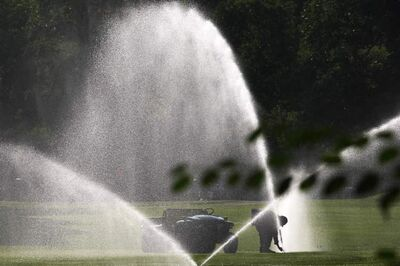 A maintenance worker adjusts sprinklers on the 18th hole of the Kildonan Golf Course Thursday morning. The fairways will be busy in coming days.