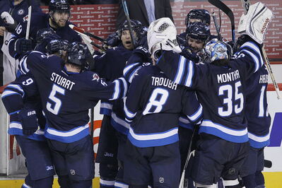 Winnipeg Jets' Blake Wheeler (26) (centre) celebrates with his team after scoring against the Colorado Avalanche for the win in NHL overtime action in Winnipeg on Wednesday, March 19, 2014.