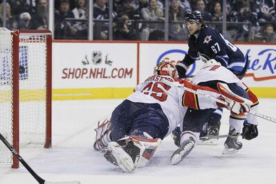 Winnipeg Jets' Michael Frolik scores on Florida Panthers goaltender Jacob Markstrom as part of a 5-2 victory Friday. The team is on its way to Vancouver to play the Canucks Sunday.
