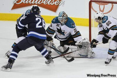San Jose Sharks' goaltender Antti Niemi (31) saves the shot from Winnipeg Jets' Blake Wheeler (26) as Sharks' Justin Braun (61) and Jason Demers (60) cover the rebound during second period NHL action in Winnipeg on Thursday.