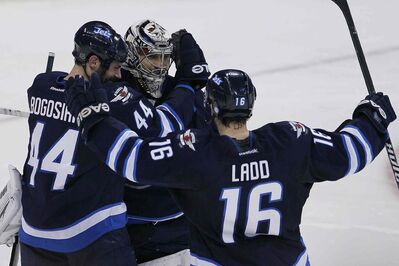 Winnipeg Jets' Zach Bogosian (44), goaltender Ondrej Pavelec (31) and Andrew Ladd (16) celebrate their NHL win over the over San Jose Sharks in Winnipeg on Sunday, November 10, 2013.