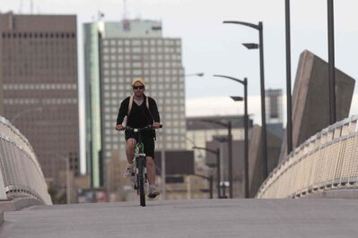 Enjoy it while you can: Calvin Bilsky on his way to work  rides over the Disraeli Active Transportation Bridge on the 7th annual Bike to Work Day. Thunderstorms and more rain are in the forecast.