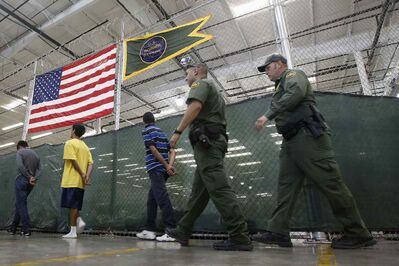 This June 18, 2014, file photo shows young detainees being escorted to an area to make phone calls as hundreds of mostly Central American immigrant children are being processed and held at the U.S. Customs and Border Protection Nogales Placement Center in Nogales, Ariz.