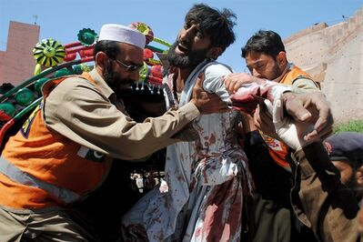 Pakistani volunteers help an injured man arriving at a local hospital in Peshawar, Pakistan on Thursday, March 21, 2013. A car packed with explosives blew up inside a refugee camp in northwestern Pakistan on Thursday as hundreds of people lined up to get food, killing and wounding dozens, police said. (AP Photo/Sohail Iqbal)