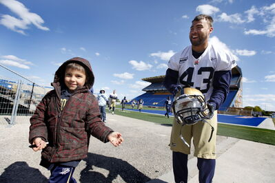 James Green signs an autograph for a young fan during has last stint with the Winnipeg Blue Bombers.