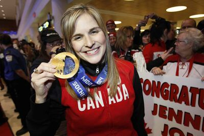 Olympic curling gold medalists Jennifer Jones shows off her gold medal to hundreds of family and supporters at the Winnipeg airport Monday night.