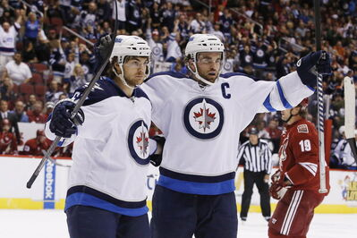Winnipeg Jets' Andrew Ladd, right, celebrates his goal against the Phoenix Coyotes with teammate Michael Frolik, left, of the Czech Republic, during the first period of Tuesday's game. The Jets won the game 2-1.