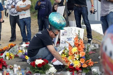 "A man views flowers and memorials at a roadside memorial at the site of the auto crash that took the life of actor Paul Walker and another man, in the small community of Valencia, Calif., Monday, Dec. 2, 2013. The neighborhood where ""Fast & Furious"" star Walker died in the one-car crash is known to attract street racers, according to law enforcement officials. Walker and his friend and fellow fast-car enthusiast Roger Rodas died Saturday when the 2005 Porsche Carrera GT they were traveling in smashed into a light pole and tree. The two had taken what was expected to be a brief drive away from a charity fundraiser at Rodas' custom car shop in the Southern California community of Valencia, about 30 miles (48 kilometers) northwest of Los Angeles. (AP Photo/Nick Ut)"