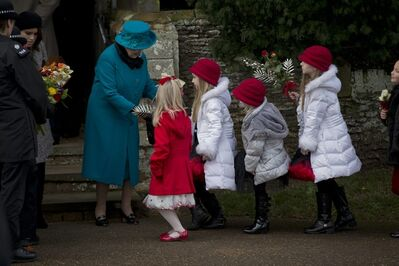 Britain's Queen Elizabeth II receives flowers from children after attending the British royal family's traditional Christmas Day church service in Sandringham, England, Tuesday.