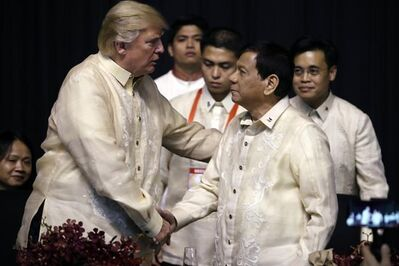 President Donald Trump, left, shakes hands with Philippines President Rodrigo Duterte at an ASEAN Summit dinner at the SMX Convention Center, Sunday, Nov. 12, 2017, in Manila, Philippines. Trump is on a five country trip through Asia traveling to Japan, South Korea, China, Vietnam and the Philippines. (AP Photo/Andrew Harnik)