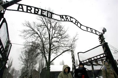 "FILE --In a Jan. 26, 2005 file photo, visitors walk under the notorious ""Arbeit Macht Frei"" sign at the entrance gate of the Auschwitz Nazi concentration camp in Oswiecim, southern Poland. The special prosecutors' office that investigates Nazi war crimes said Tuesday Sept. 3, 2013 it is recommending charges against dozens of alleged former Auschwitz guards, opening the possibility of a new wave of trials almost 70 years after the end of World War II. Kurt Schrimm, the head of the Ludwigsburg federal prosecutors' office, said an investigation of about 50 alleged former guards turned up enough evidence to recommend that state prosecutors pursue charges of accessory to murder against 30 of them in Germany. (AP Photo/Herbert Knosowski/file)"