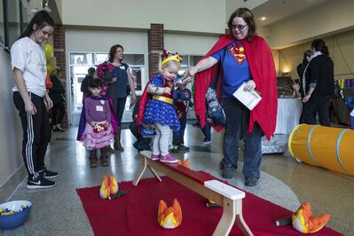 MIKE DEAL / WINNIPEG FREE PRESS</p><p>Kierstin Bage, 2, and her sidekick/mom, Brenda, traverse a bridge above a raging fire during a Superhero Brunch at the Caboto Centre Sunday morning. The event was put on as a fundraiser for a new non-profit organization called Frosting Foundation, which provides birthday party supplies to children who are in the hospital. </p>