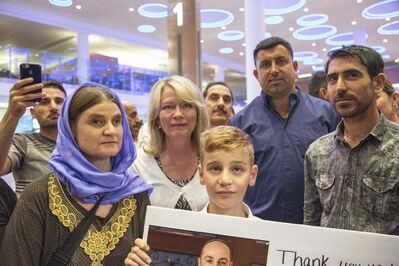 JUSTIN SAMANSKI-LANGILLE / WINNIPEG FREE PRESS</p><p>Emad Mishko Tamo, 12, centre, his mother Nofa Mihlo Rafo, left, and uncle Hadji Tamo move through a large crowd of supporters and media at Winnipeg's James Armstrong Richardson International Airport early Thursday morning.</p>
