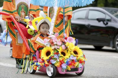 Dressed in traditional garb, this youngster navigates a spiffed up toy car through the street festival.</p>