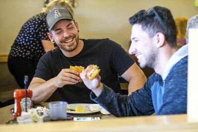 DANIEL CRUMP / WINNIPEG FREE PRESS</p><p>Happy customers Kyle Pimental (left) and Camilo Olivar (right) chow down on the Le Burger Week special at Southdale Village Family Restaurant.</p>