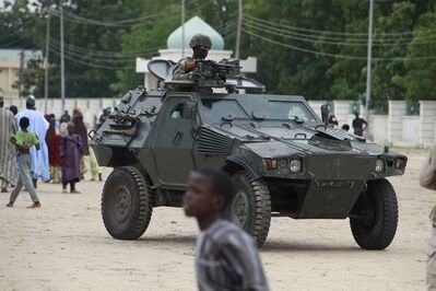 """FILE - In this Thursday, Aug. 8, 2013 file photo, Nigerian soldiers ride on an armored personnel carrier during Eid al-Fitr celebrations in Maiduguri, Nigeria. Hundreds of people are dying in military detention as Nigeria's security forces crack down on an Islamic uprising in the northeast, Amnesty International said Tuesday, Oct. 15, 2013. Some people are shot outright, some starve and others suffocate to death, it said. """"Others were reportedly shot in the leg during interrogations, provided no medical care and left to bleed to death,"""" the London-based human rights group said in a new report that includes testimony from freed detainees. More than 950 people died in military custody in the first six months of this year, according to """"credible information"""" from a senior Nigerian army officer, it said. If true, that would mean that Nigeria's military has killed more civilians than the extremists during the first half of 2013. (AP Photo/Sunday Alamba file)"""