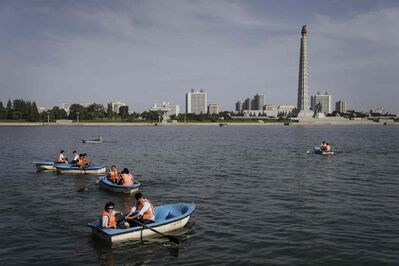 North Koreans row their boats past the Juche Tower which overlooks the Taedong River, Sunday, Aug. 31, 2014 in Pyongyang, North Korea.