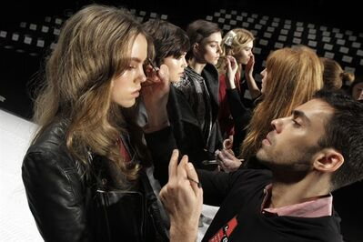 """Models have their make-up finalized under runway light before the J. Mendel Fall 2012 collection is modeled during Fashion Week, in New York. The 19 editors of Vogue magazines around the world made a pact to project the image of healthy models. They agreed to """"not knowingly work with models under the age of 16 or who appear to have an eating disorder"""" and they will ask casting directors to check IDs at photo shoots, fashion shows and for ad campaigns, according to a Conde Nast International announcement Wednesday.(AP Photo/Richard Drew, file)"""