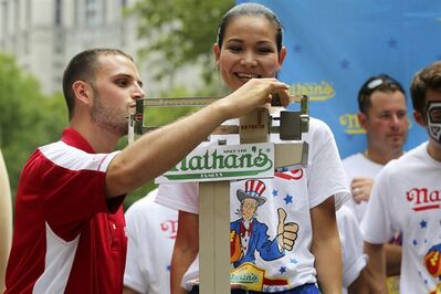 Sonya Thomas smiles as she stands on the scale during the official weigh-in for the Nathan's Fourth of July hot dog eating contest, Wednesday, July 3, 2013 at City Hall park in New York. (AP Photo/Mary Altaffer)