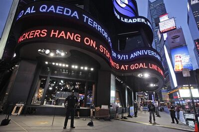 "A police officer stands guard in New York's Times Square as the ABC news ticker displays news of an al-Qaida terror threat, Friday, Sept. 9, 2011. Just days before the 10th anniversary of the Sept. 11 attacks, U.S. counterterrorism officials are chasing a credible but unconfirmed al-Qaida threat to use a car bomb on bridges or tunnels in New York City or Washington. It is the first ""active plot"" timed to coincide with the somber commemoration of the terror group's 9/11 attacks a decade ago that killed nearly 3,000 people. (AP Photo/Mary Altaffer)"