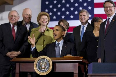 President Barack Obama, surrounded by members of Congress, looks up while signing the farm bill on Feb. 7, 2014, at Michigan State University in East Lansing, Mich. From left: Sen. Carl Levin, D-Mich., Senate Agriculture Committee member Sen. Patrick Leahy, D-Vt. Senate Agriculture Committee Chair Sen. Debbie Stabenow, D-Mich., Senate Agriculture Committee member Sen. Amy Klobuchar, D-Minn., Agriculture Secretary Tom Vilsack, Rep. Marcia Fudge, D-Ohio and Rep. Gary Peters, D-Mich.