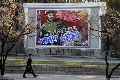 "A man walks by a poster reading ""Severe punishment to the U.S. and their followers"" in the central district of Pyongyang, North Korea, on Thursday, May 2, 2013. (AP Photo/Jon Chol Jin)"