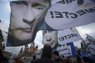 "People rally in support of Crimea joining Russia, with banners and portraits of Russian President Vladimir Putin, reading ""We are together,"" in Red Square in Moscow on Tuesday, March 18, 2014."