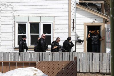One of two suspects exits a house Winnipeg police had surrounded on Selkirk Avenue Sunday afternoon.