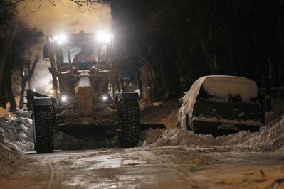 A grader clears snow on McGee Street Sunday night.