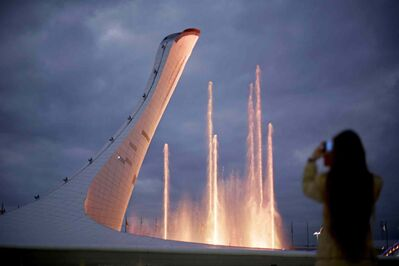 A spectator takes a photo during the testing of a water light show at the Olympic cauldron in the Olympic Park at the 2014 Winter Olympics, Saturday, in Sochi, Russia.