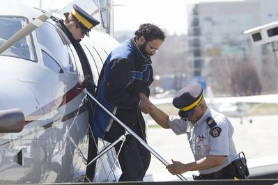 Chiheb Esseghaier, one of two men accused of plotting a terror attack on a rail target, is led off a plane by RCMP officers at Buttonville Airport north of Toronto in April.
