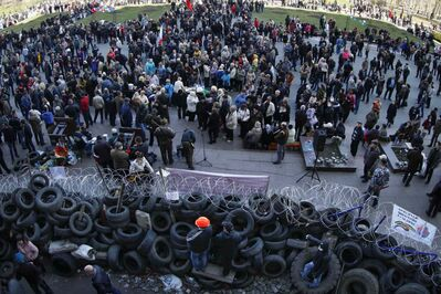 People gather in front of a barricade at the regional administration building in Donetsk, Ukraine Monday.