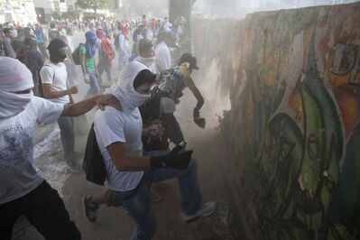 Demonstrators destroy a wall in order to have more rocks to throw at the Bolivarian National Guard during anti-government protests in Caracas, Venezuela, Tuesday, March 4, 2014. A year after the death of Hugo Chavez, Venezuela has been rocked by weeks of violent protests that the government says have left 18 dead. President Maduro appears ready to use Chavez's almost mythical status to steady his rule as protesters refuse to leave the streets.
