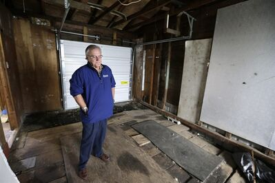 In this photo taken Monday, Sept. 23, 2013, Dann Sears, curator of the Aberdeen Museum of HIstory, stands in the tiny garage of the childhood home of Kurt Cobain, the late frontman of Nirvana, in Aberdeen, Wash. Cobain's mother is putting the tired, 1.5-story Aberdeen bungalow on the market this week, the same month as the 20th anniversary of Nirvana's final studio album. The home, last assessed at less than $67,000, is being listed for $500,000, but the family would also be happy entering into a partnership with anyone who wants to turn it into a museum. (AP Photo/Elaine Thompson)