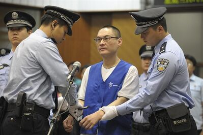 Han Lei, center, is handcuffed by police officers after his verdict was read in a court in Beijing, China Wednesday, Sept. 25, 2013. The court convicted Han and sentenced him to death for hurling a toddler to the ground in a case that horrified the Chinese public. (AP Photo) CHINA OUT