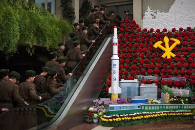 North Korean soldiers ride an escalator past a model of their country's Unha Rocket as they enter an exhibition in Pyongyang on Sunday, Feb. 17, 2013 where Kimjongilia flowers, named after the late North Korean leader Kim Jong Il, were on display. (AP Photo/David Guttenfelder)