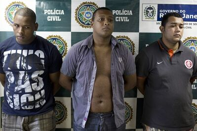 Suspects Wallace Aparecido Souza Silva, left, Carlos Armando Costa dos Santos, center, and Jonathan Foudakis de Souza are presented to the press at the Special Police Unit for Tourism Support (DEAT) after being arrested for allegedly attacking tourists in Rio de Janeiro, Brazil, Tuesday, April 2, 2013. An American woman was gang raped and beaten aboard a public transport van while her French boyfriend was shackled, hit with a crowbar and forced to watch the attacks after the pair boarded the vehicle in Rio de Janeiro's showcase Copacabana beach neighborhood, police said. The attacks took place over six hours starting shortly after midnight on Saturday. (AP Photo/Felipe Dana)