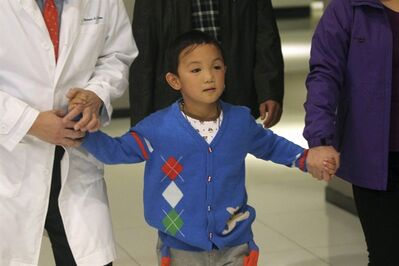 Guo Bin, a 6-year-old Chinese boy who received prosthetic eyes, walks to a press conference at a hospital in Shenzhen in south China's Guangdong province Thursday Dec. 12, 2013. The boy whose eyes were gouged out in an attack more than three months ago was discharged Thursday from the hospital where he was successfully fitted with prosthetic eyes. (AP Photo) CHINA OUT