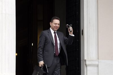 Greek Finance Minister Yannis Stournaras waves to reporters as he arrives at Maximos' Mansion to meet with Greek Prime Minister Antonis Samaras and the debt inspectors from the European Central Bank, European Commission and International Monetary Fund, known as the troika in Athens on Sunday, April 7, 2013. (AP Photo/Kostas Tsironis)