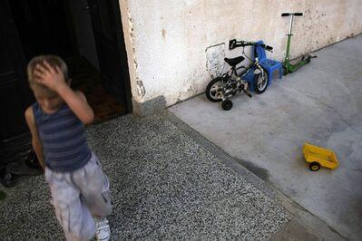 In this photo taken on Wednesday, Sept. 14, 2011, Luka Lukic, 6, exits his home in Gornji Milanovac, some 100 kilometers (60 miles) south of Belgrade, Serbia. Serb cousins David and Luka are poles apart from other kids, for when it comes to metalwear, everything sticks. The two boys from the central Serbian town of Gornji Milanovac have a rare ability to attract metal objects, acting much like human magnets. (AP Photo/ Marko Drobnjakovic)