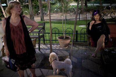 In this photo taken on Sunday, June 2, 2013, Israeli Orthodox Jew Shahar Hadar, right, rests between two shows outside a drag queen school in downtown Tel Aviv, Israel. Hadar, a telemarketer by day, has taken the gay Orthodox struggle from the synagogue to the stage, beginning to perform as one of Israel's few religious drag queens. His drag persona is that of a rebbetzin, a female rabbinic advisor, a wholesome guise that stands out among the sarcastic and raunchy cast of characters on Israel's drag queen circuit. (AP Photo/Oded Balilty)