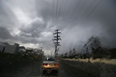 The view is distorted as the windshield of a car is covered in water as a driver makes his way through stormy weather after unusually heavy rainfall caused localized flooding in Sochi, Russia, Tuesday, Sept. 24, 2013. Many critics still complain about underdeveloped infrastructure in Sochi, where the Olympics will be held in February 2014. (AP Photo/Sergei Grits)