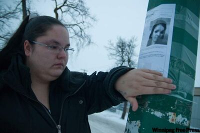 Ashley Geddes, sister of Amber Guiboche, puts up posters about the missing woman Saturday in the North End.