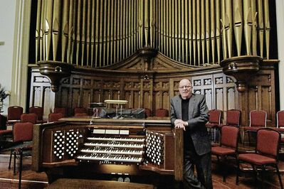 Don Menzies stands in front of Westminster's pipe organ. The massive instrument is valued at $1.7 million. Menzies has been the organist for 51 years.