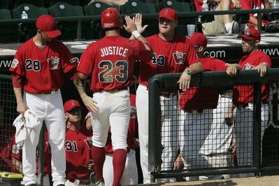 Winnipeg Goldeyes manager Rick Forney (43) hands out a high-five to Justin Justice after the Goldeyes outfielder went deep against Kansas City on Sunday.
